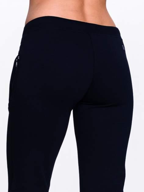 Czarne spodnie dresowe z kwiatem z dżetami i przeszyciem                                  zdj.                                  7