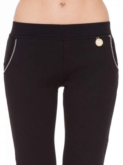 Czarne spodnie dresowe z łańcuszkami przy kieszeniach                                  zdj.                                  5