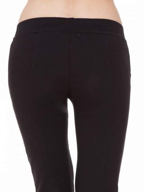 Czarne spodnie dresowe z łańcuszkami przy kieszeniach                                  zdj.                                  8