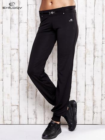 Czarne spodnie dresowe z ozdobnym paskiem                                  zdj.                                  1