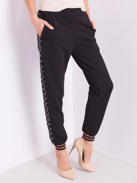 Czarne spodnie dresowe z ozdobnymi lampasami                              zdj.                              5