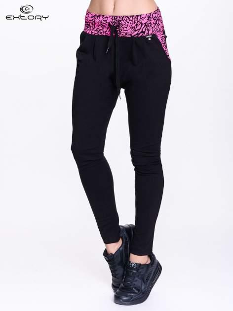Czarne spodnie dresowe z różowym pasem w panterkę                                  zdj.                                  1