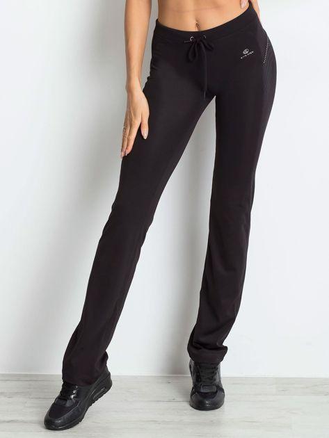 Czarne spodnie z troczkami i wzorkiem po boku                              zdj.                              1