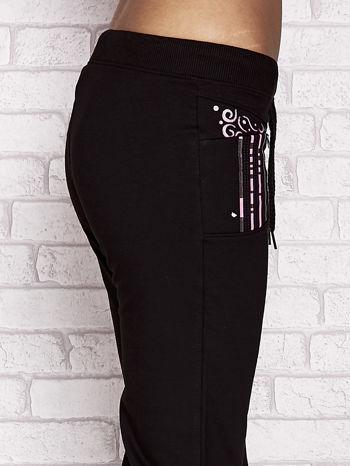 Czarno-różowe spodnie dresowe capri z dziewczęcymi nadrukami                                  zdj.                                  5