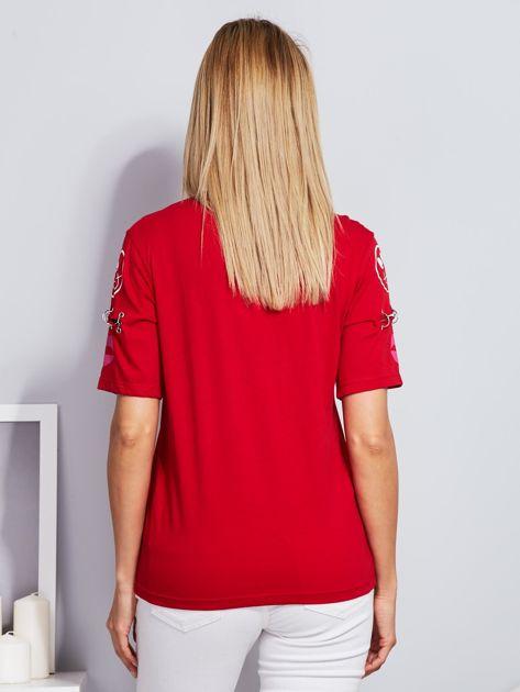 Czerwony t-shirt z napisem i kółeczkami na rękawach                                  zdj.                                  2