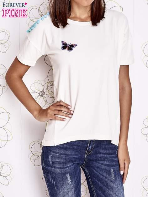 Ecru t-shirt z naszywką motyla i pomponami                                  zdj.                                  1