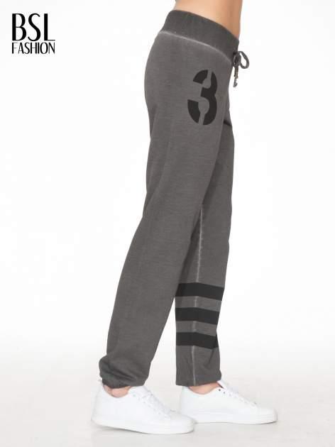 Grafitowe dresowe spodnie damskie z numerkiem i paskami na nogawkach                                  zdj.                                  3
