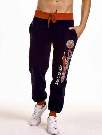 Granatowe dresowe spodnie męskie z napisem CALIFORNIA i naszywką                                  zdj.                                  1