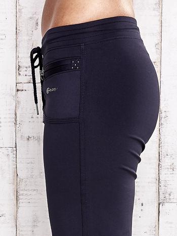 Granatowe spodnie capri z dżetami i kieszonką                                  zdj.                                  5