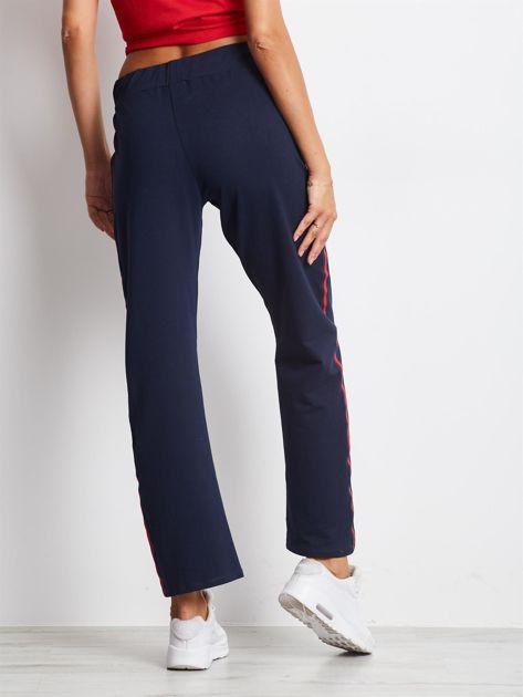 Granatowe spodnie dresowe z lampasami                              zdj.                              2