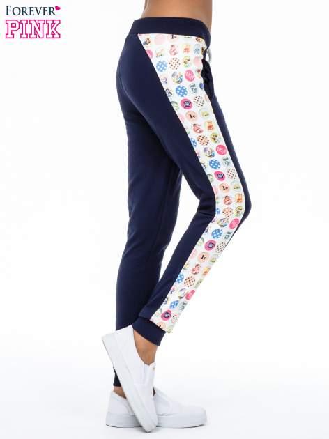 Granatowe spodnie dresowe z lampasem w znaczki                                  zdj.                                  3