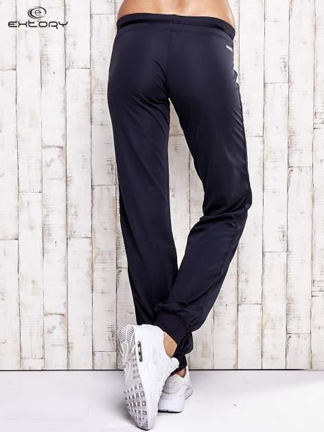 Granatowe spodnie dresowe z ozdobnym paskiem                                  zdj.                                  3