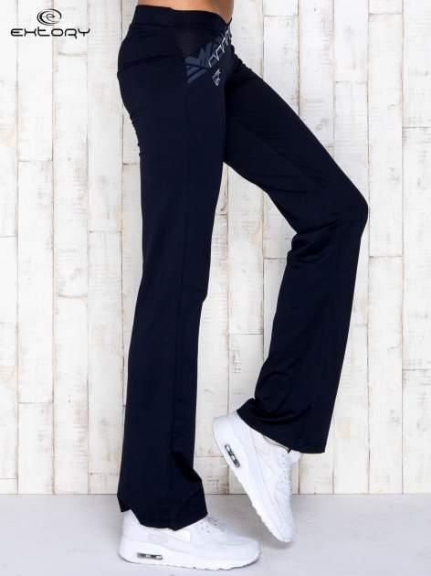 Granatowe spodnie dresowe z srebrnymi wstawkami                                  zdj.                                  2