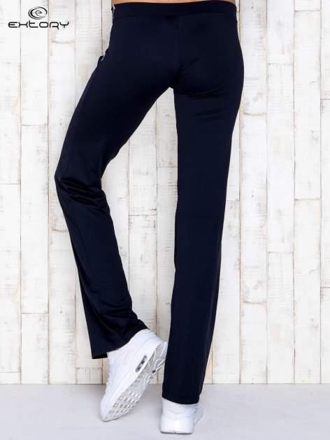 Granatowe spodnie dresowe z srebrnymi wstawkami                                  zdj.                                  3