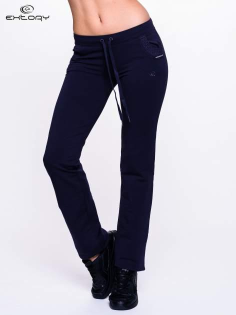 Granatowe spodnie dresowe ze wzorzystą wstawką przy kieszeniach