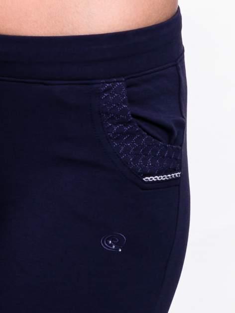 Granatowe spodnie dresowe ze wzorzystą wstawką przy kieszeniach                                  zdj.                                  5