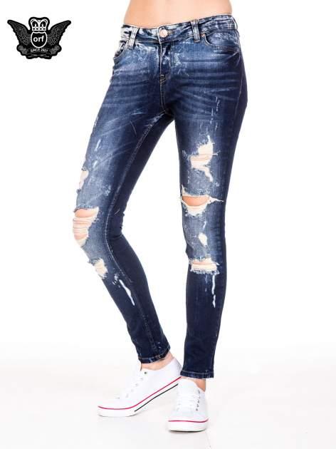 Granatowe spodnie jeansowe rurki z poszarpanymi nogawkami                                  zdj.                                  1