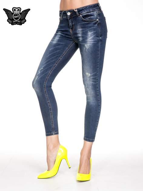 Granatowe spodnie skinny jeans z przecieraną nogawką z przodu                                  zdj.                                  1