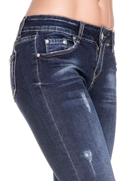 Granatowe spodnie skinny jeans z zamkami na dole                              zdj.                              5