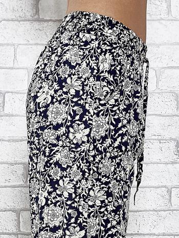 Granatowe zwiewne spodnie alladynki we wzór kwiatków                                  zdj.                                  6