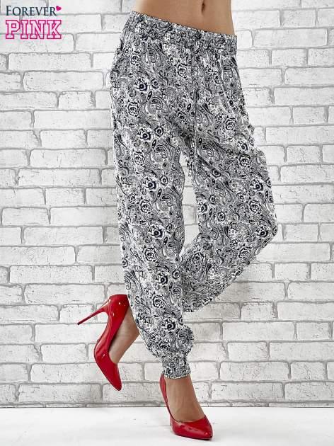 Granatowe zwiewne spodnie alladynki we wzór roślinny
