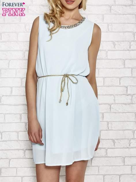 Jasnoniebieska sukienka ze złotym łańcuszkiem przy dekolcie