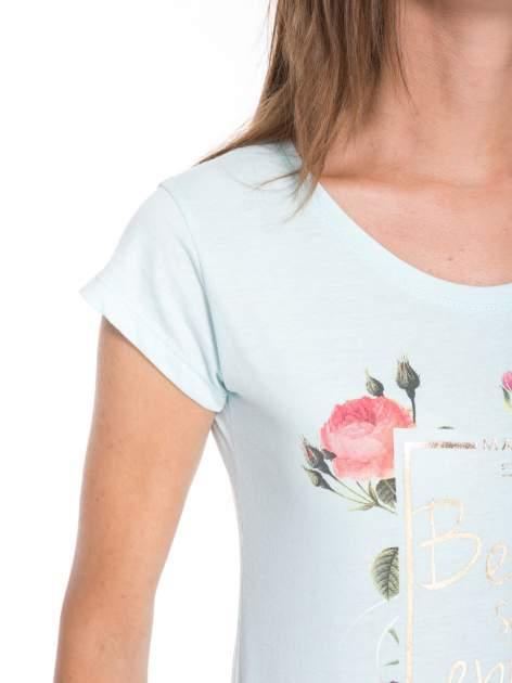Jasnoniebieski t-shirt z kwiatowym nadrukiem i złotym napisem                                  zdj.                                  7