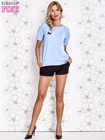 Jasnoniebieski t-shirt z naszywką motyla i pomponami                                  zdj.                                  4