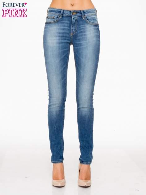 Jasnoniebieskie spodnie jeansowe rurki z przeszyciami na kieszeniach