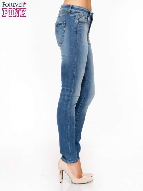 Jasnoniebieskie spodnie jeansowe rurki z przeszyciami na kieszeniach                                  zdj.                                  3
