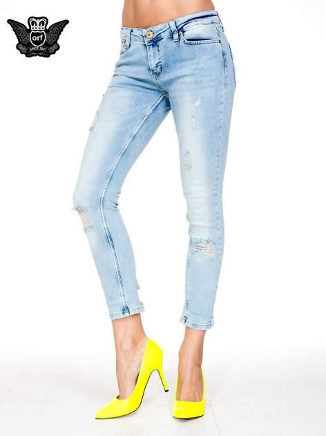 Jasnoniebieskie spodnie skinny jeans z rozdarciami na kolanie                                  zdj.                                  1