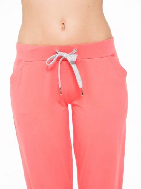 Koralowe spodnie sportowe typu capri wiązane w pasie                                  zdj.                                  6