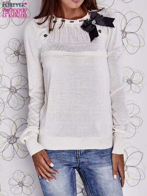 Kremowy sweter z aplikacją i kokardą przy dekolcie