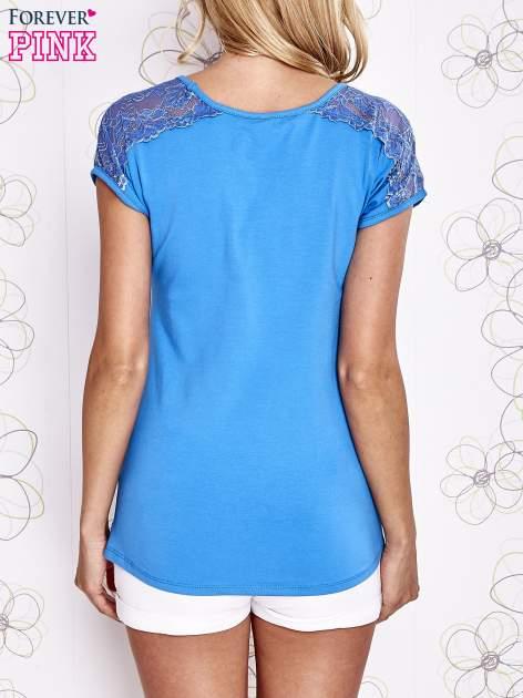 Niebieski t-shirt z koronkowym wykończeniem rękawów                                  zdj.                                  4