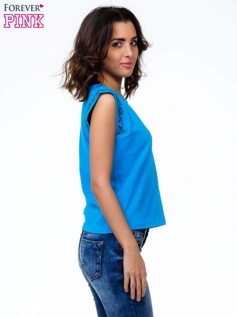 Niebieski t-shirt z ornamentem na rękawach                                  zdj.                                  3
