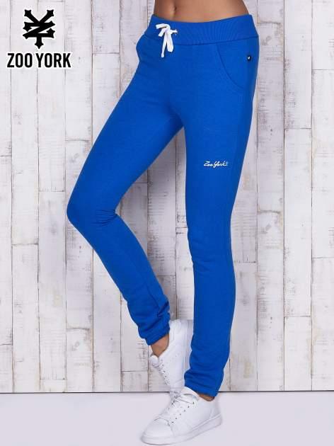 Niebieskie dopasowane spodnie dresowe ze ściągaczem w pasie
