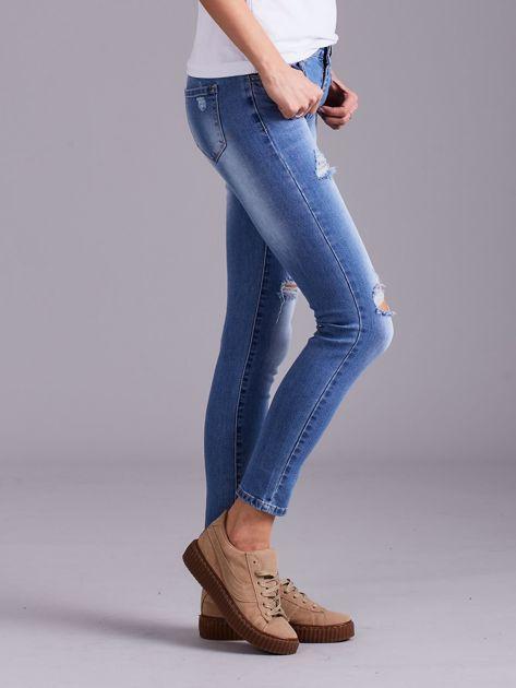 Niebieskie jeansy damskie z przetarciami                              zdj.                              3