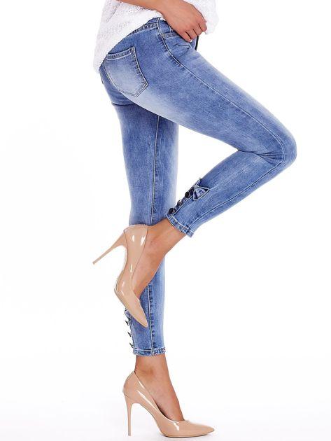 Niebieskie jeansy z guzikami na nogawkach                              zdj.                              3