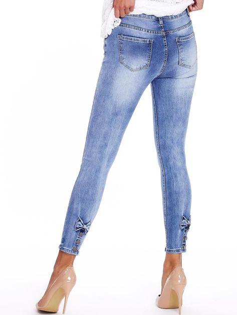 Niebieskie jeansy z guzikami na nogawkach                              zdj.                              2