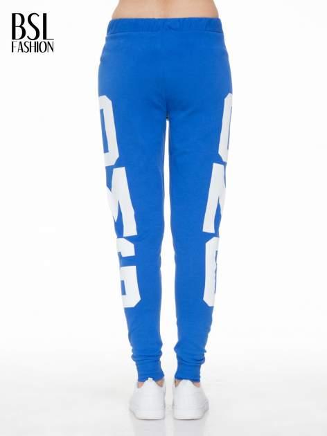 Niebieskie spodnie dresowe z nadrukiem OMG z boku nogawek                                  zdj.                                  4