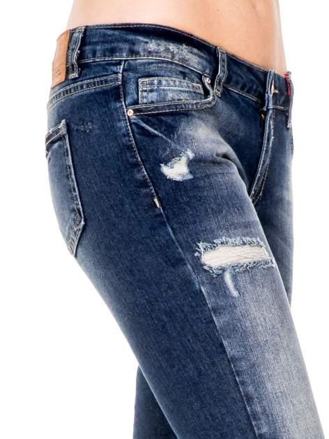 Niebieskie spodnie girlfriend jeans z rozjaśnianą nogawką i dziurami                                  zdj.                                  6