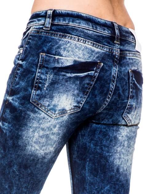 Niebieskie spodnie jeansowe rurki z cieniowaniem i rozdarciami na kolanach                                  zdj.                                  8