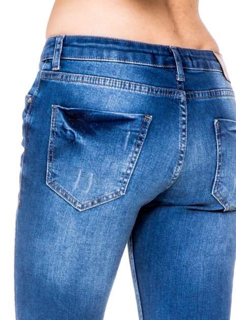 Niebieskie spodnie jeansowe rurki z dziurami i wytarciami                                  zdj.                                  6