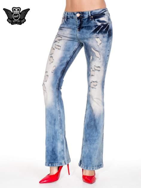 Niebieskie spodnie jeasnowe dzwony z przetarciami i rozjaśnianą nogawką                                  zdj.                                  1
