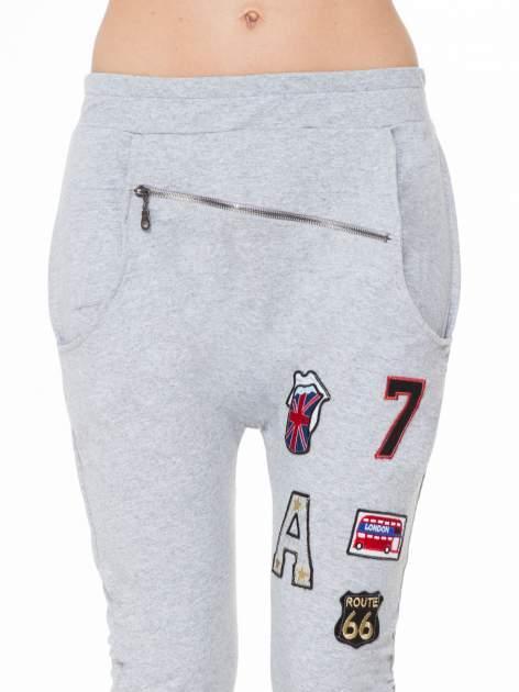 Szare spodnie dresowe typu baggy z naszywkami                                  zdj.                                  5