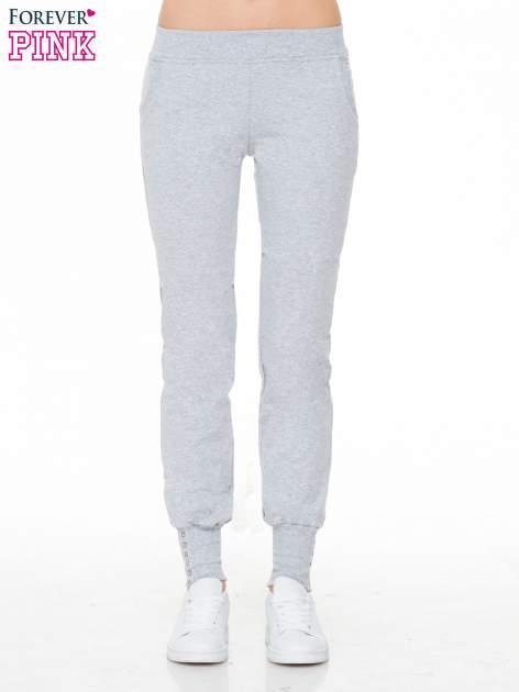 Szare spodnie dresowe z guziczkami przy ściągaczach nogawek