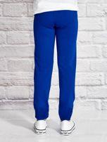 Ciemnoniebieskie spodnie dresowe dla dziewczynki z nadrukiem serc                                  zdj.                                  2