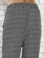 Czarne zwiewne spodnie alladynki w drobny wzór geometryczny                                  zdj.                                  7