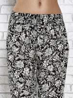 Czarne zwiewne spodnie alladynki we wzór kwiatków