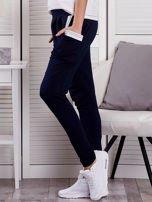 Granatowe spodnie dresowe ze ściągaczami przy kieszeniach                                  zdj.                                  3